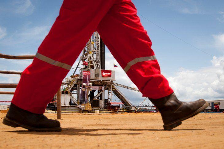 FOTO DE ARCHIVO. Un trabajador pasa junto a una plataforma de perforación en un pozo petrolero operado por la petrolera estatal venezolana PDVSA