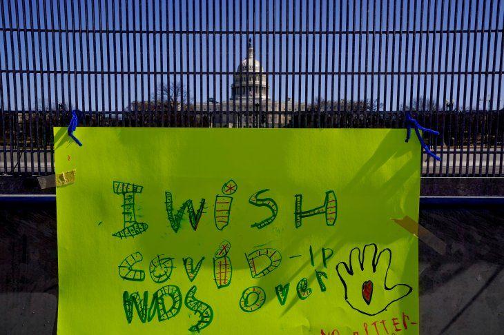 FOTO DE ARCHIVO: Una pancarta en la que se lee Ojalá la COVID-19 fuera cosa del pasado en inglés colgada en la verja de seguridad que rodea el Capitolio en Washington D. C.