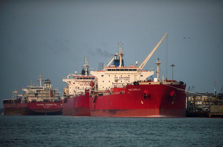 Un remolcador pasa por un petrolero atracado en el puerto de Tuxpan