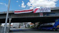 El micro con el plantel de Boca, pasando por un punte de la autopista en La Paz.