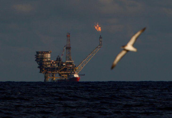 Imagen de archivo de una gaviota volando frente a una plataforma petrolera en el Campo Bouri