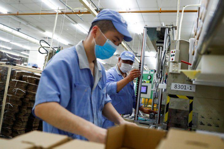 Foto de archivo de empleados usando mascarillas en una fábrica en Pekín