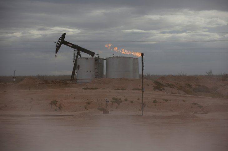 FOTO DE ARCHIVO: Una bomba de petróleo y una llamarada de la combustión del exceso de gas en una instalación de perforación petrolífera en la Cuenca Pérmica situada en el condado de Loving County