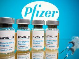 FILE PHOTO: Vials with a sticker reading, COVID-19 / Coronavirus vaccine / Injection only and a medical syringe are seen in front of a displayed Pfizer logo in this illustration taken October 31,