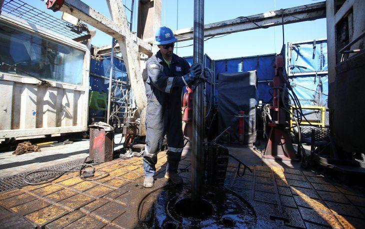 Foto de archivo. Trabajador limpia una plataforma de perforación de petróleo y gas de esquisto en el yacimiento Vaca Muerta
