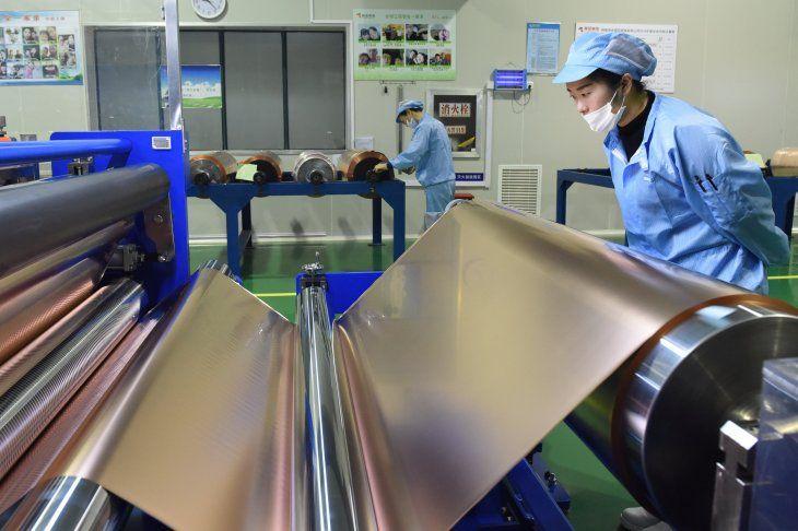 FOTO DE ARCHIVO. Empleados trabajan en una línea de producción de láminas de cobre utilizadas para baterías de litio