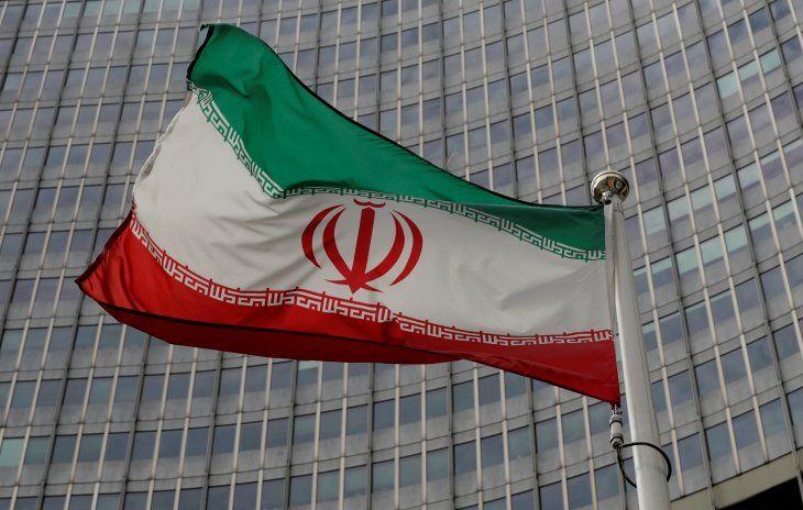 Imagen de archivo de una bandera iraní ondeando frente a la sede central del Organismo Internacional de Energía Atómica (OIEA) en Viena