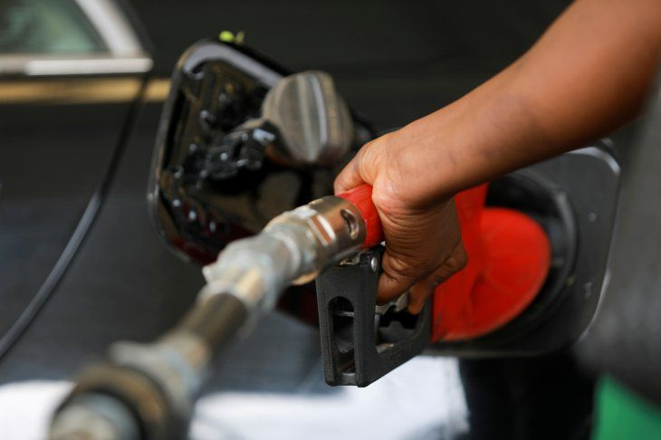 Imagen de archivo de un empleado de una estación de combustible cargando gasolina en el automóvil de un cliente en una estación de NNPC Mega en Abuya