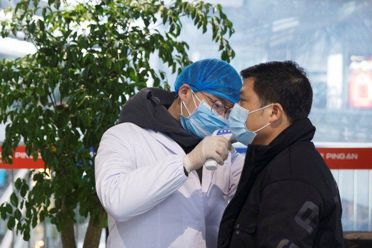 Un trabajador de salud toma la temperatura corporal a un hombre en la sala de embarques del aeropuerto de Changsha