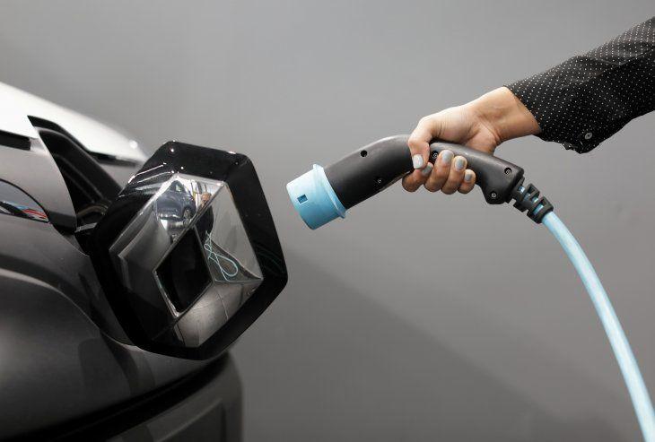 Imagen de archivo de una mujer sosteniendo un cable para cargar un vehículo utilitario deportivo eléctrico Renault Kangoo ZE en un concesionario automotor de Renault en Cagnes-Sur-Mer